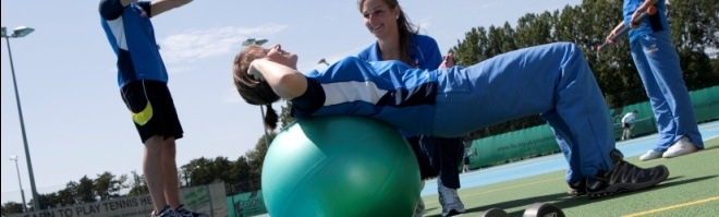People exercising outside on exercise ball