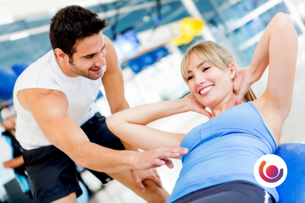 personal trainer helping female client do sit ups