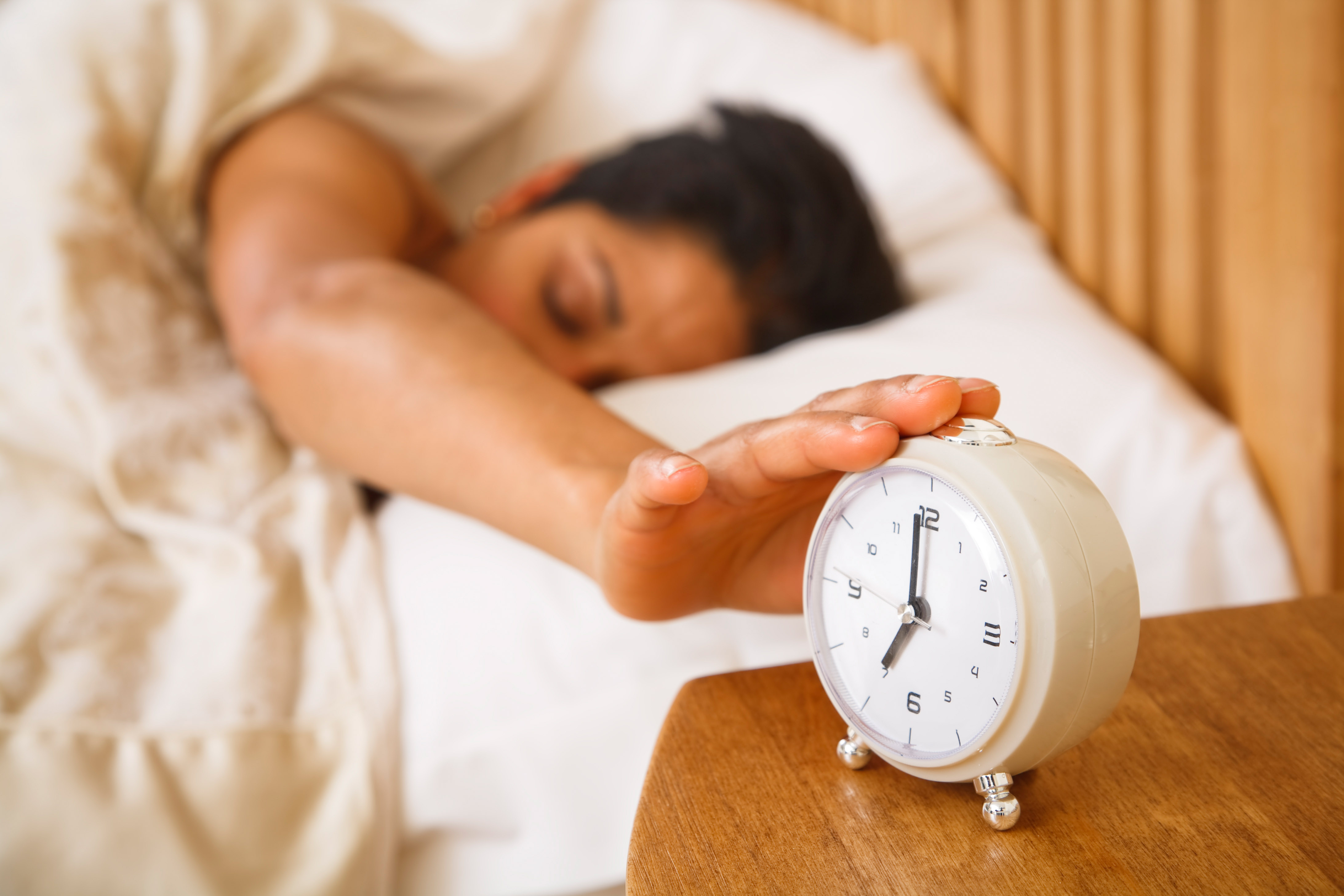 Sleepy Woman Reaching for Alarm Clock