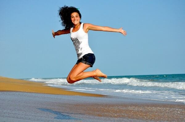 woman jumping on the beach looking happy
